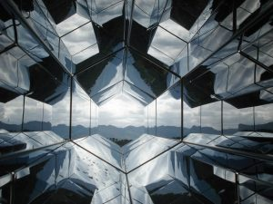 ID: A landscape phot of a series of honeycomb-shaped mirrors, reflecting the view of a mountain range in the distance. End ID.